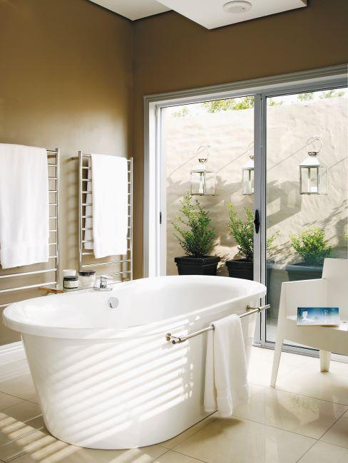 salle de bain avec baignoire, fauteuil design blanc et grande fenêtres ouvert sur le jardin