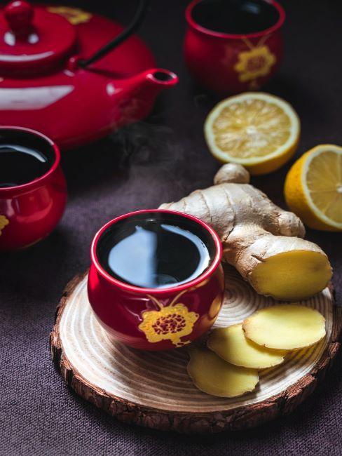Thé au gingembre dans une tasse rouge sur plateau en bois