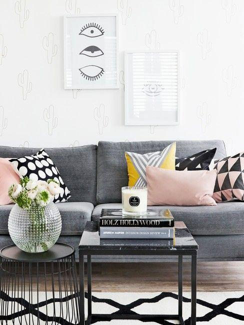 canapé gris, murs blancs, coussins multicolores, cadres blancs sur les murs