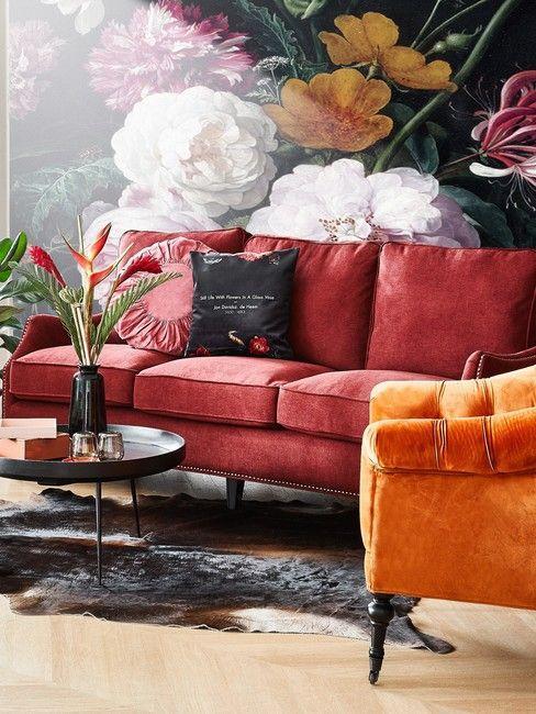 canapé velours rouge, papier peint fleuris, gros motifs, fauteuil rouge rouille, table basse ronde, vase avec fleurs, salon baroque, glamour