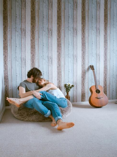 Couple qui se fait un câlin installé sur un pouf avec une guitare