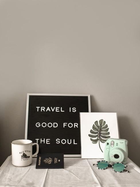 Tableau avec une inscription sur le voyage, une tasse et un appareil photo polaroid posés sur une table