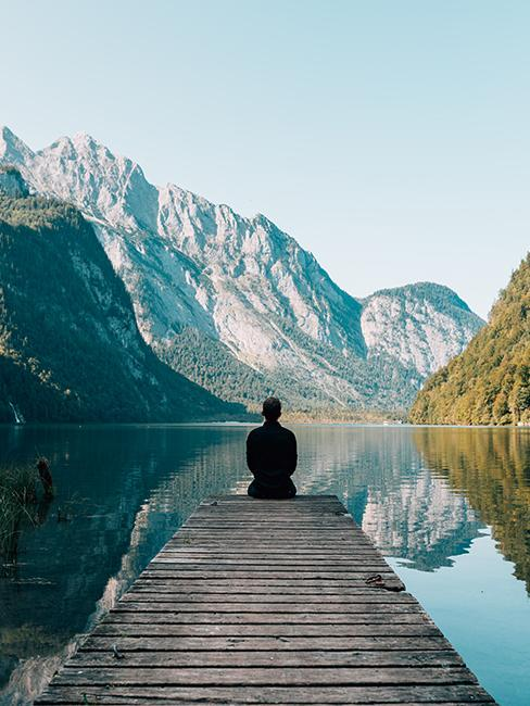 personne assise sur un ponton au bord d'un lac