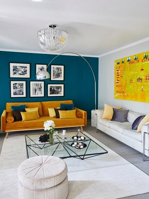 Salon avec canapé orange et beige avec pleins de coussins, mur bleu et décoration murale,