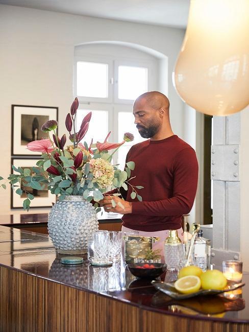 Ampio vaso in cucina con ragazzo che decora con fiori