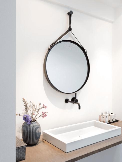Bagno cieco con lavabo bianco e specchio tondo