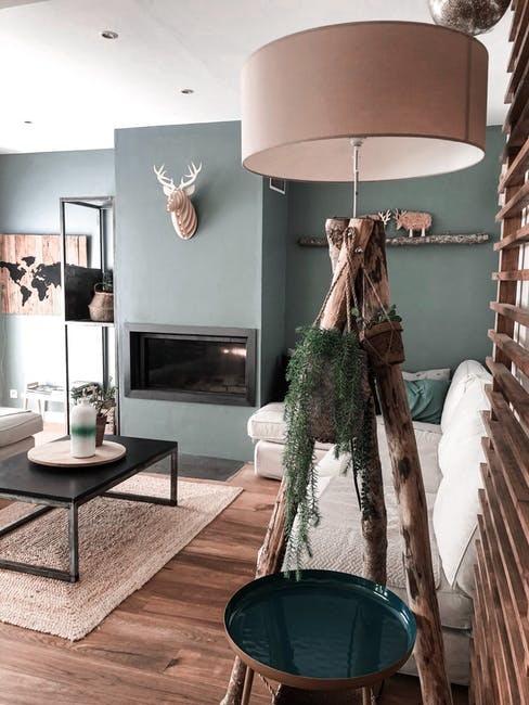 Soggiorno con lampada da terra in legno ed elementi naturali