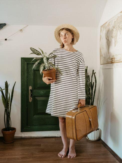 ragazza con vestito a righe con valigia di pelle