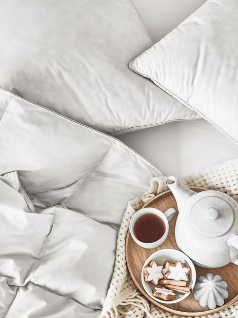 vassoio con tè e biscotti sopra a letto sfatto