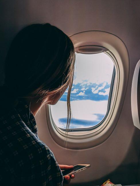 donna in aereo che guarda fuori dal finestrino