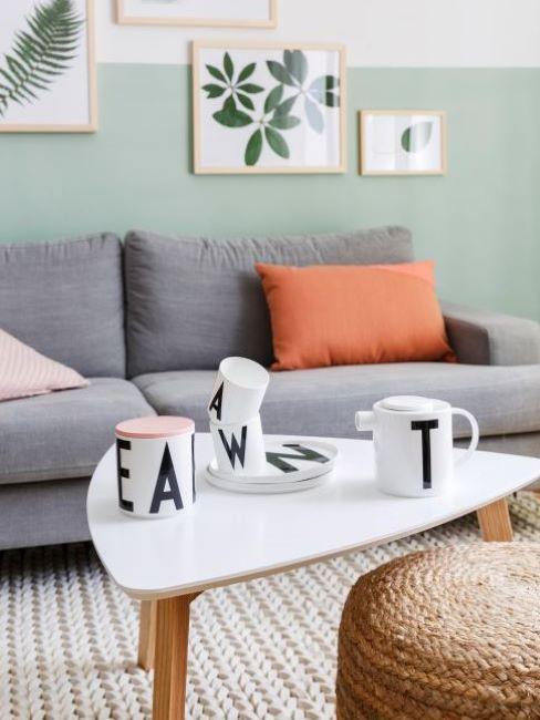 soggiorno con parete verde menta, divano grigio e cuscini cantaloupe