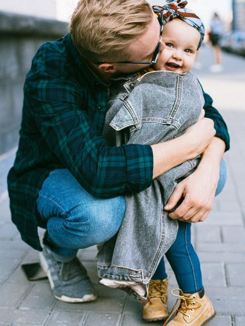papà giovane che abbraccia figlia piccola
