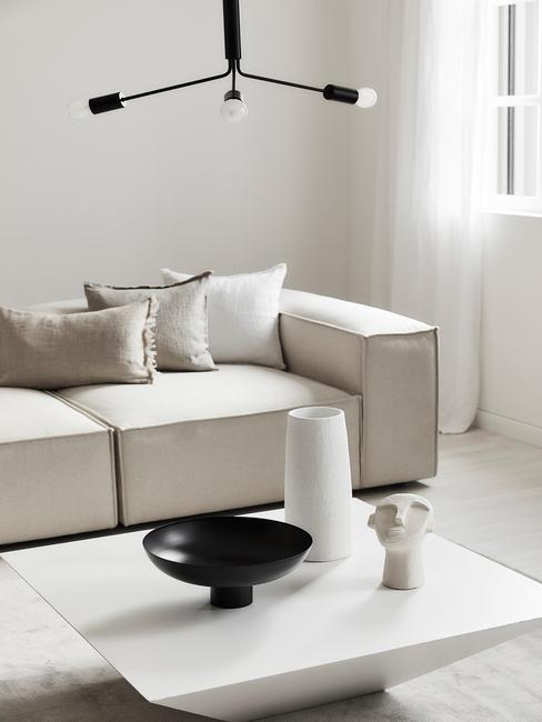 Een woonkamer met witte zitbank en salontafel in betonlook
