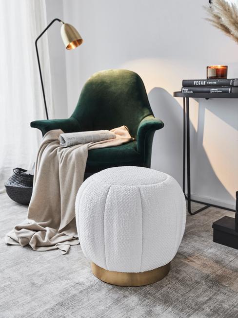 Boucle witte poef naast een groene fluwelen fauteuil met beige zachte plaid