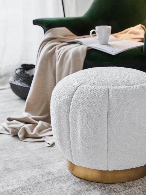 Boucle witte poef naast een groene fluwelen fauteuil