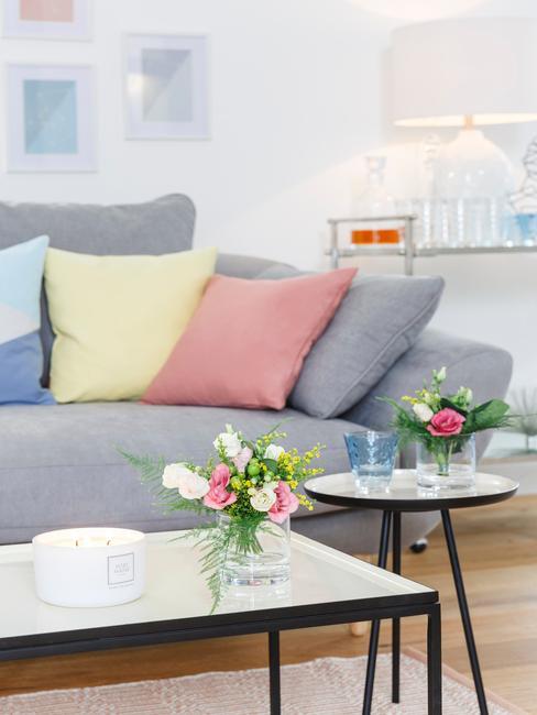 Glazen salontafel naast een zitbank in grijs met sierkussens in roze en geel