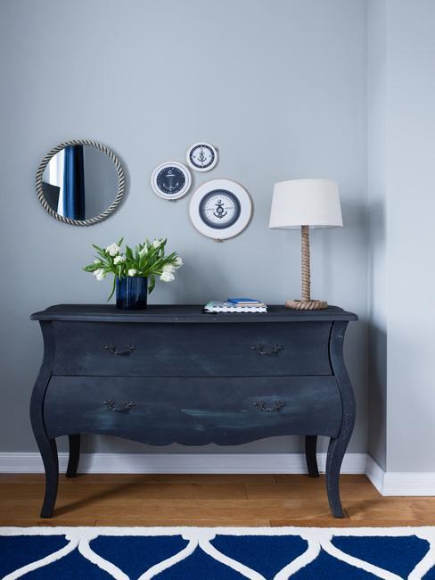 Batik: houteen sideboard in blauw met decoratieve wandobjecten en tafellamp