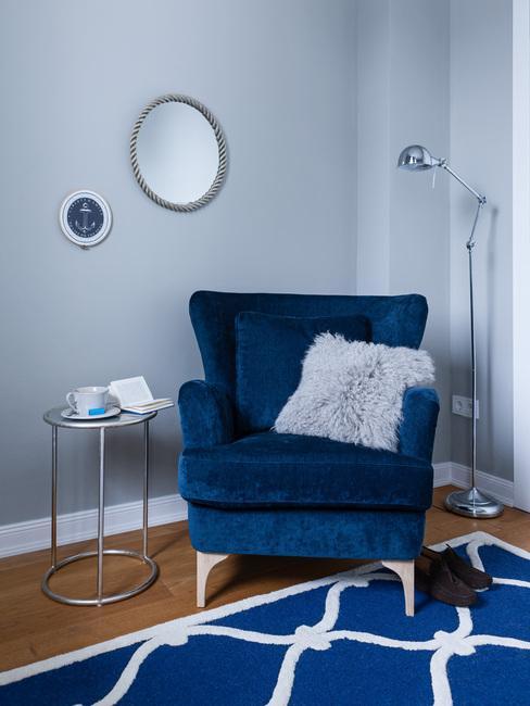 Donkerblauwe fluwelen fauteuil met sierkussen op blauw vloerkleed