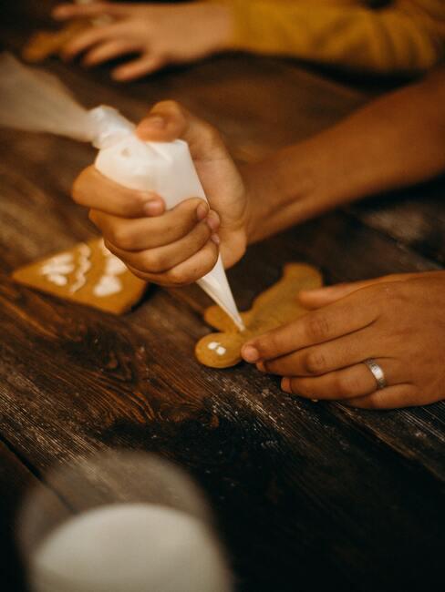 Vrouw versieren kerst gebakken goederen in de keuken