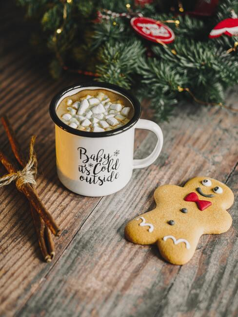 Kerstkoekjes met kop melk naast een kerstkrans