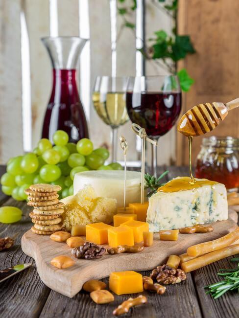 Diverse kazen en olijven, druiven en andere snacks en rode wijn in wijnglas