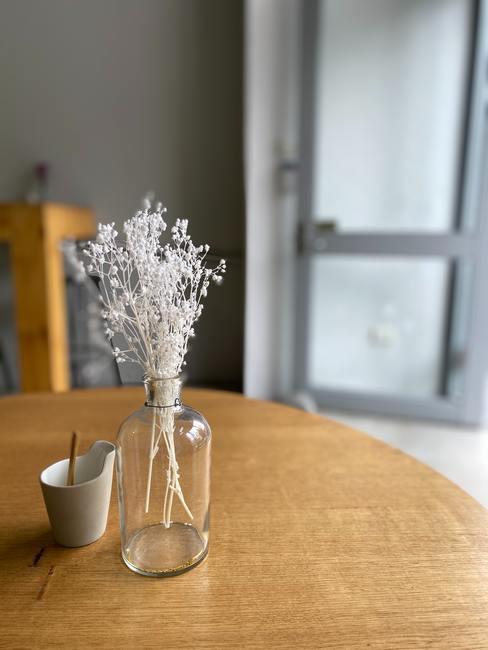 Kunsttakje in een transparante glazen vaas op een houten ronde tafel