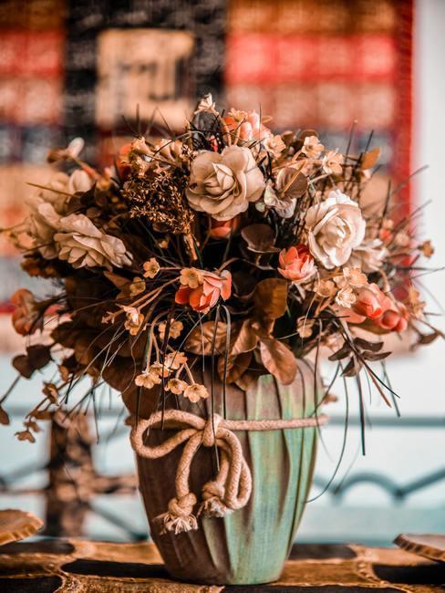 Een monumentaal boeket kunstbloemen in boho stijl in een prachtige vaas op bijzettafel