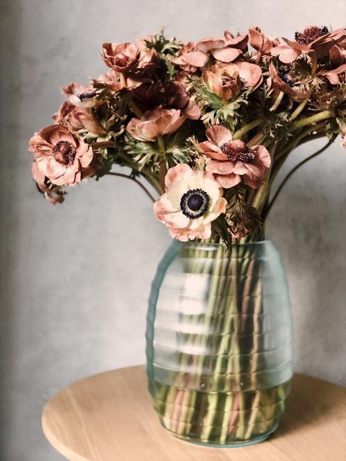 Een bescheiden boeket met kunstbloemen in een transparante glazen vaas