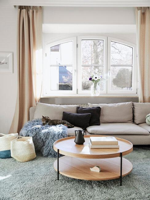 Woonkamer met beige bank grijs vloerkleed en houten tafel