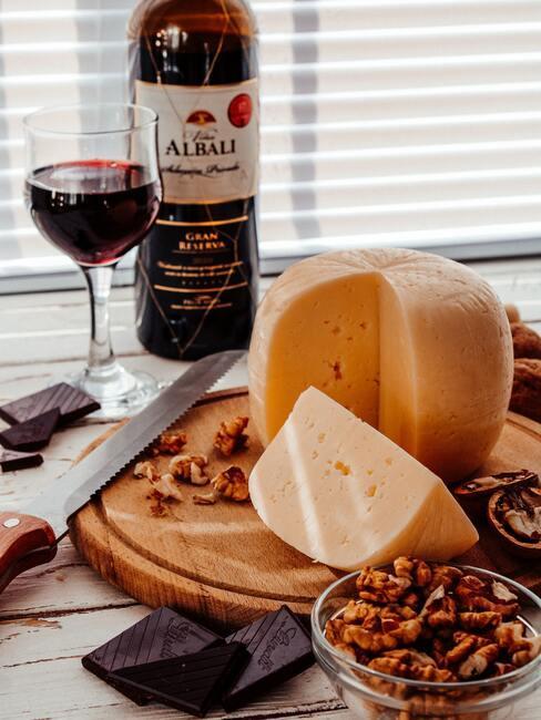 Rode wijn in glas naast een kaasplank