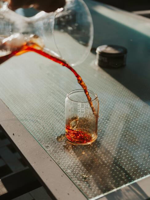 Vrouw zelfgemaakte wijn uit een karaf gieten in een glas