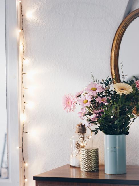 Decoratie van bloemen in lichtblauwe vaas met een lichtketting en spiegel op de muur