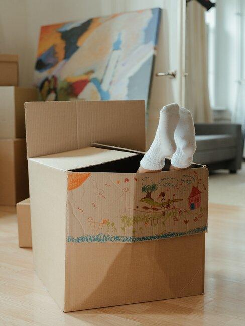 jongensvoeten steken uit handgekleurde doos in jongenskamer