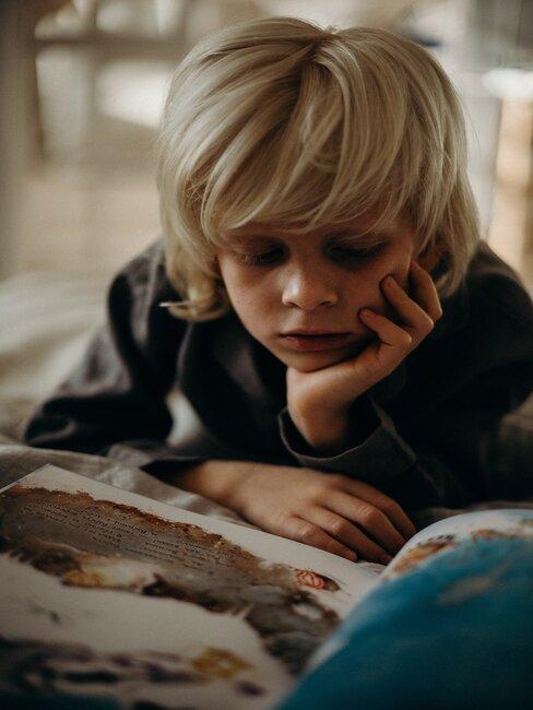 jongen leest prentenboek op bed