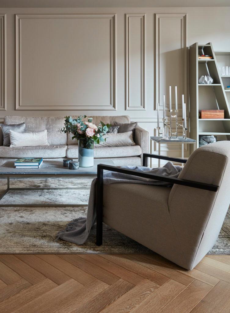 Grote taupe armleunstoel met grijs plaid in design woonkamer