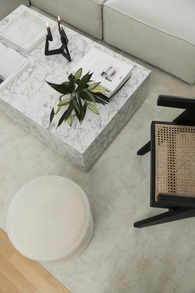 marmeren bijzettafel met witte poef en rotan stoel