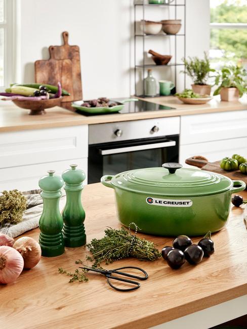 Groene potten en zoutmolens op een houten bord