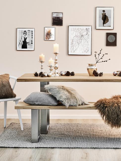 Houten eettafel met verschillende accesoires en grijze zitkussens en prints op de muur