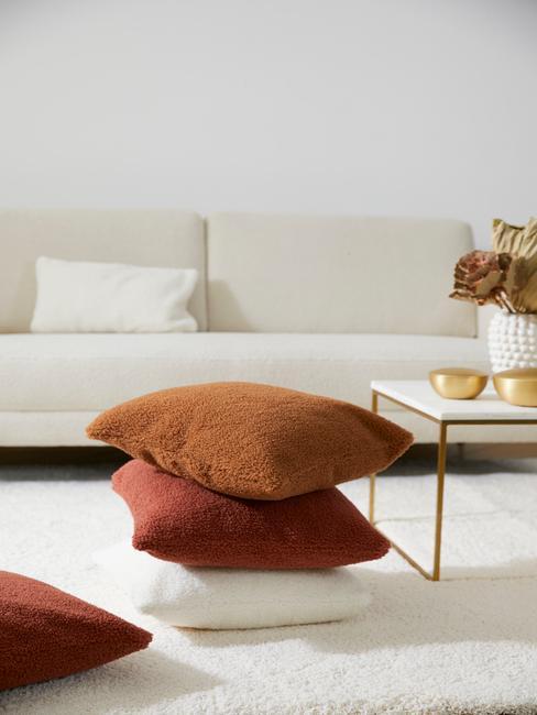 Kussens in wit, bruin en oranje op wit vloerkleed naast een witte salontafel