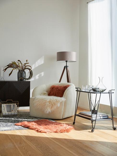 Witte Teddy fauteuil met bruin sierkussen naast een zwarte bijzettafel en teddy vacht