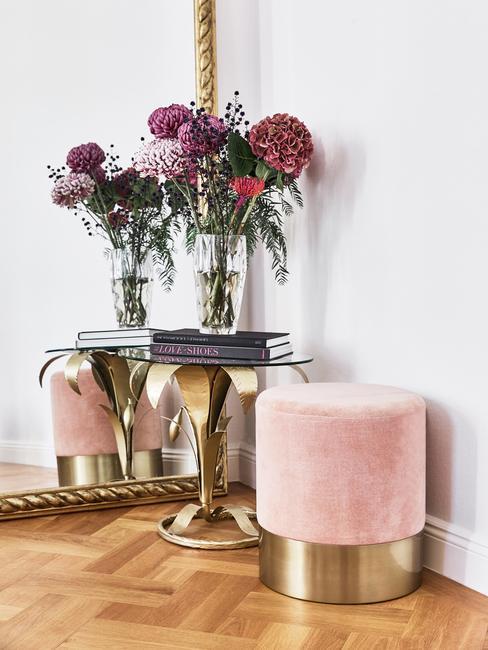 Fluwelen kruk naast een bijzettafel van geborsteld metaal met transparant vaas met bloemen