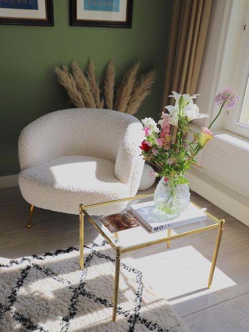 Witte teddy vacht fauteuil naast een glazen bijzettafel met transparante glazen vaas met bloemen