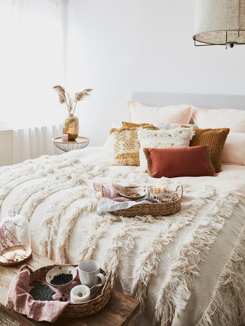 Kleurrijke sierkussens op bed in slaapkamer