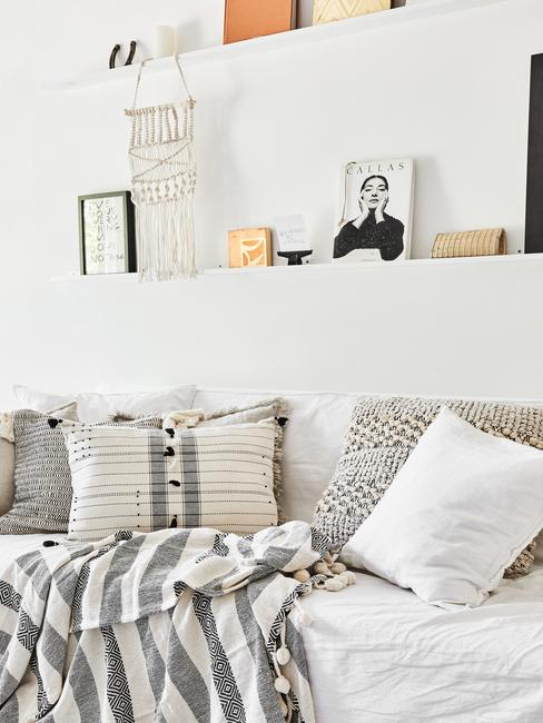 Woonkamer in wit met comfortabele zitbank met plaid met franjes en sierkussens in grijs en beige
