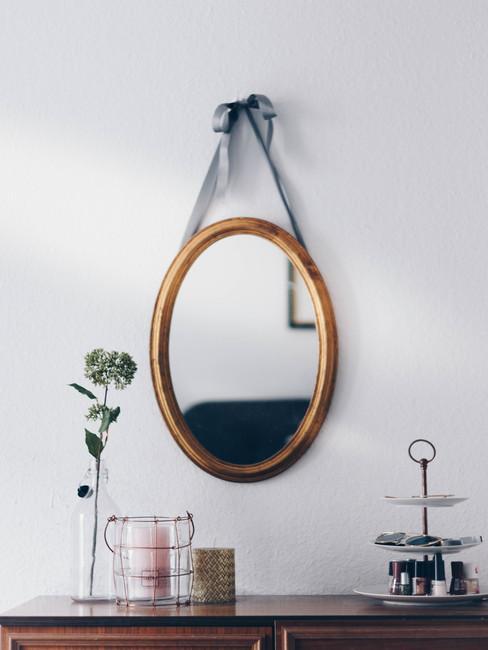 Een decoratieve spiegel op een witte muur en een houten dressoir met vaas en etagere.