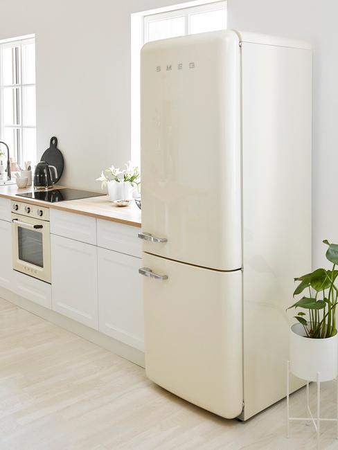 opgeruimde witte keuken met witte smeg koelkast