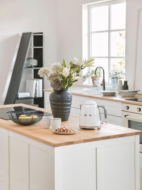 eiland in lichte keuken met witte smeg waterkoker en zwarte vaas met bos bloemen