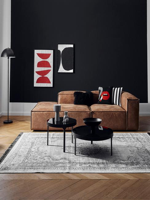 Moderne woonkamer met zwarte muur met ingelijste prints en suede zitbank met sierkussens, zwarte bijzettafels en groot vloerkleed