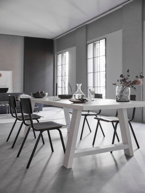 industrieel interieur witte eetkamertafel met zwarte stoelen