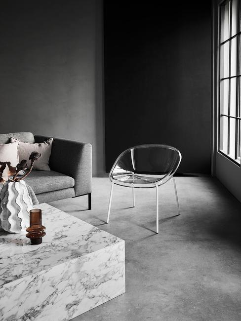 industrieel interieur woonkamer met marmere koffietafel en transparante stoel